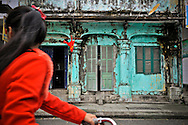 A young Vietnamese girl looks over her shoulder as she rides her bicycle past an old weathered facade, Hue, Vietnam, Southeast Asia