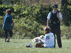 © Licensed to London News Pictures. 20/04/2020. London, UK. A police officer moves a person sunbathing on Primrose Hill, north London during a pandemic outbreak of the Coronavirus COVID-19 disease. The public have been told they can only leave their homes when absolutely essential, in an attempt to fight the spread of coronavirus COVID-19 disease. Photo credit: Ben Cawthra/LNP. Photo credit: Ben Cawthra/LNP