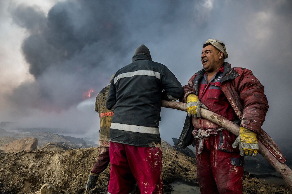 Firefighters from Kirkuk, Iraq work the line of fires that stretch for many miles. The hours are long and they have no special equipment. Water is their only weapon. Qayyara, Iraq. Nov. 23, 2016. (Photo by Gabriel Romero ©2016)