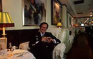 Hong Kong. David Tang ar the china Club.   /  David Tang au China club en train de se faire cirer les chaiussures par un garde ?rouge?. Tang un chinois iconoclaste qui passe sa vie entre Hongkong et Londres. Il a installé le Club le plus chic, le plus cher et le plus branché de Hongkong au 11 em étage de la banque de Chine (communiste), à l'intérieur il a reconstitué l'ambiance de Shangai des annèes 20.   /  295542/    L940322a  /  R00225  /  P0006705