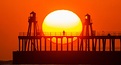 © Licensed to London News Pictures. 23/03/2020. Whitby UK. A man stands alone on Whitby pier watching the sunrise this morning on the Yorkshire coast as the Government continues to urge people to follow social distancing advice & stay two metres apart. Photo credit: Andrew McCaren/LNP