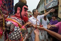 © Licensed to London News Pictures. 18/10/2015 Batu Gajah, Perak, Malaysia. A devotee in a emperor god costume hands out treats to people lining the parade route during the Nine Emperor Gods Festival celebration in Batu Gajah, Malaysia, Sunday, Oct. 18, 2015. Photo credit : Sang Tan/LNP