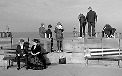 © Licensed to London News Pictures.01/11/15<br /> Whitby, UK. <br /> <br /> A group of youngsters stand on the seawall as a goth couple sit on a bench as they attend the Whitby Goth weekend in Whitby, North Yorkshire. The event began in 1994 to celebrate goth culture and music and takes place twice each year. <br /> Thousands of extravagantly dressed people attend the popular event wearing Steampunk, Cybergoth, Romanticism, Victoriana and other clothing as they take part in the celebration of Goth culture. <br /> <br /> Note to Editors - Picture shot on Kodak Tri X 400ISO film.<br /> Photo credit : Ian Forsyth/LNP