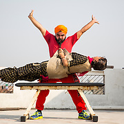 PUNJAB, INDIA - NOVEMBER, 14, 2016: Ranjeet Singh, 35, a beard weight lifter, lifts 40 kg (88 lb) girl Lovepreet Kaur, 20,  with his beard at his gym in Ludhiana, a city in Punjab, India. <br />