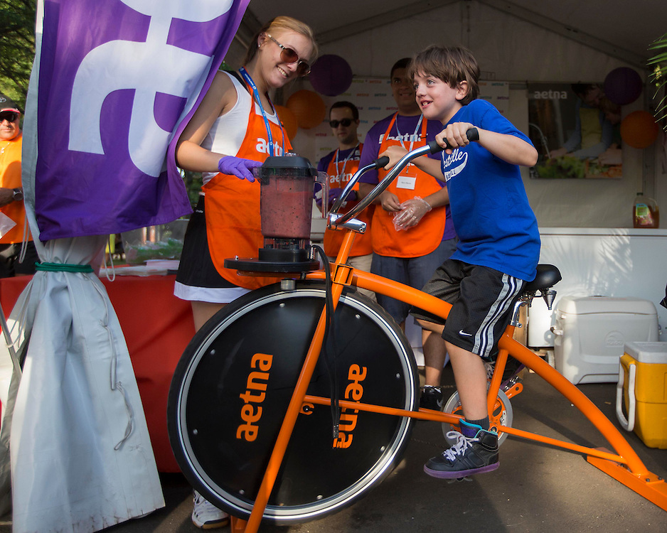 August 16, 2014, New Haven, CT:<br /> A fan rides on the Aetna smoothie bike during Military Night on day four of the 2014 Connecticut Open at the Yale University Tennis Center in New Haven, Connecticut Monday, August 18, 2014.<br /> (Photo by Billie Weiss/Connecticut Open)