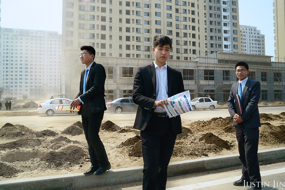 Young estate agents, who are children of farmers, wait for clients in front of commercial residential blocks built over farmland. Their families have lost their farmland, and now they are peddling apartment blocks to buyers.