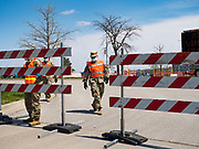 "26 APRIL 2020 - DES MOINES, IOWA: Soldiers with the Iowa Army National Guard open the gate of the COVID-19 drive through testing site in Des Moines. Iowa started mass testing Saturday, with a drive through testing site in a parking lot in downtown Des Moines. The testing this weekend is considered a ""soft opening"" for the program and tests were reserved for medical professionals and first responders. Despite numerous outbreaks in meat packing plants throughout Iowa, members of the public have not been able to get tested. On Saturday, 25 April, there were 5,092 confirmed cases of COVID-19 (Coronavirus / SARS-CoV-2) in Iowa (an increase of 647 since Friday, April 24) and 112 deaths in Iowa caused by COVID-19.PHOTO BY JACK KURTZ"