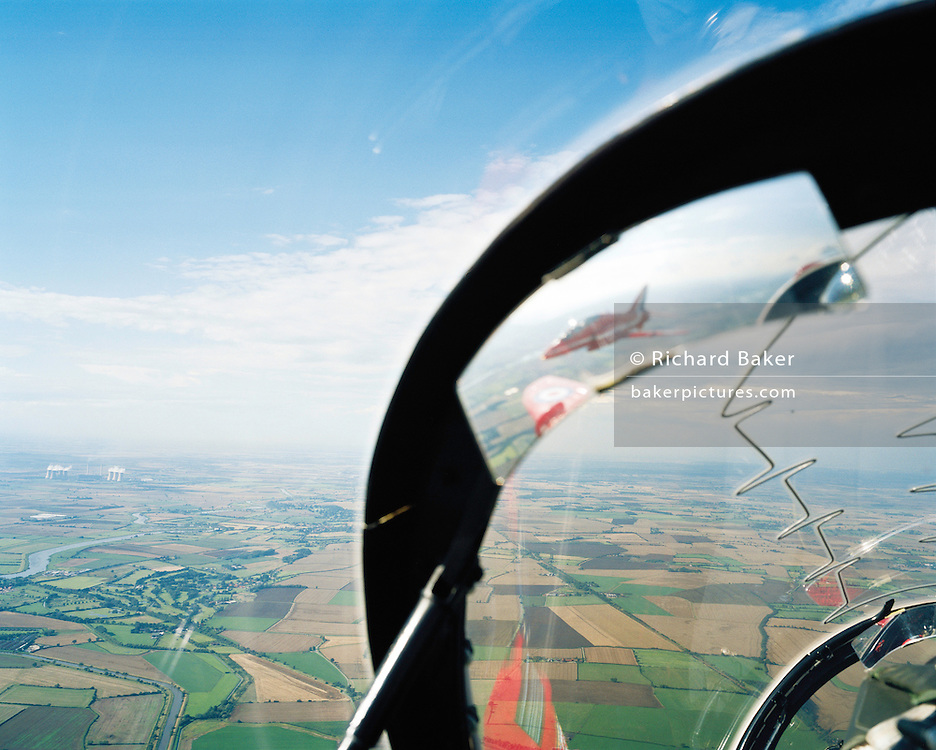 Seen from the cockpit of another Hawk of the elite 'Red Arrows', Britain's Royal Air Force aerobatic team during an In-Season Practice (ISP) training flight near their base at RAF Scampton. Seen through the explosive Plexiglass cockpit of a tenth plane, we see forward into deep blue sky as two sets of aerobatic pilots steer their machines from a crossover manoeuvre, their organic white smoke pouring from their jet pipes to emphasize their paths through the air. In front of a local crowd at the airfield the team work their way through a 25-minute series of display manoeuvres that are loved by thousands at summer air shows. After some time off, spare days like this are used to hone their manual aerobatic and piloting skills before re-joining the air show circuit. Since 1965 they've flown over 4,000 shows in 52 countries.
