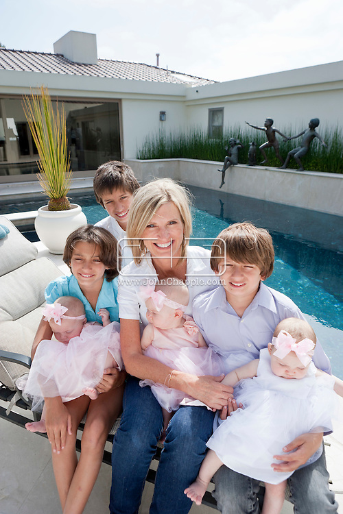 6th May 2011. Dana Point, California. DeAun Nixon, who has given birth to a set of triplets for herself and a set of surrogate triplets for her friend. DeAun is picture with 11-year-old triplets, Nicholas (purple shirt), Thamas and Lexi Bhardwaj and 6 month old triplets, Tatiani (white dress), Alexandra and Cozette Dodge.Photo © John Chapple / www.chapple.biz