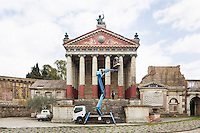 "ROME, ITALY - 30 MARCH 2015: Maintenance workers employed at Cinecittà Studios paint a Roman temple of the set of ""Rome"", the British-American-Italian broadcasted between 2005 and 2007 on HBO, BBC Two and RaiDue, here in Cinecittà, Rome, Italy, on March 30th 2015.<br /> <br /> Italy instated a special 25% tax credit for film productions in 2010. The industry then lobbied to remove the credit's cap, and last July, Italy lifted its tax credit limit from €5 million per movie to €10 million per company per year. <br />  <br /> Cinecittà, a large film studio in Rome, is considered the hub of Italian cinema. The studios were founded in 1937 by Benito Mussolini as part of a scheme to revive the Italian film industry. In the 1950s, the number of international productions being made here led to Rome being dubbed as the ""Hollywood on the Tiber"". In the 1950s, Cinecittà was the filming location for several large American film productions like Ben-Hur, and then became the studio most closely associated with Federico Fellini.<br /> After a period of near-bankruptcy, the Italian Government privatized Cinecittà in 1997, selling an 80% stake.<br /> <br /> Currently Ben-Hur and Zoolander 2 are booked into Cinecittà Studios."