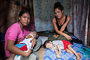 UK celebrity Myleene Klass weeps as Vilma Tacuyo, 20, holds her youngest child, Ulderico (10 months), in their one room home in an urban slum in Paranaque City, Metro Manila, The Philippines on 18 January 2013. Vilma had raised her first 3 children on formula and had to cut down on food for her family to afford it. Both John Ashley, 4, and Justin (sleeping), 3, are malnourished and stunted, and after losing one of her children, she now breastfeeds her youngest, Ulderico. Photo by Suzanne Lee for Save the Children UK