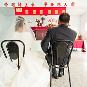 Bride and groom sit and listen to pastor's speech during their wedding ceremony. Namasiya Township, Kaoshiung County, Taiwan