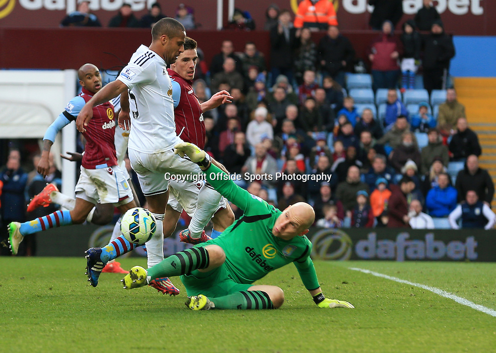 21st March 2015 - Barclays Premier League - Aston Villa v Swansea City - Aston Villa keeper Brad Guzan saves at the feet of Wayne Routledge of Swansea City - Photo: Paul Roberts / Offside.