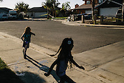 Samantha Olivarez, 9, left, and her cousin, Daisy Olivarez, 7, play in front of their home in Arvin, Calif. The homes across the street from Olivarez were evacuated after a gas pipe leaked underground. According to reports, the 40-year-old pipe was leaking for a long as two years before it was detected. Olivarez's family is worried about possible health risks in the area due to the pollution.