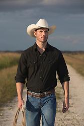 All American cowboy on a dirt road at sundown good looking cowboy outdoors