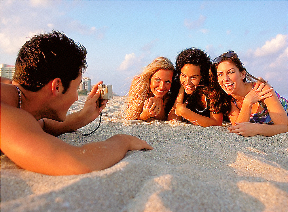 Man taking picture of three women on beach