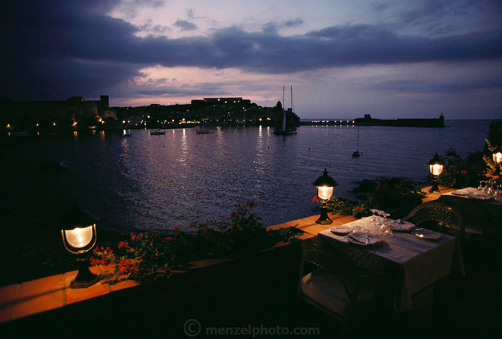 Restaurant tables ready for dinner at dusk overlooking the harbor at Collioure, France.
