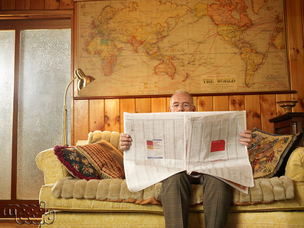 Senior man sitting on sofa reading newspaper