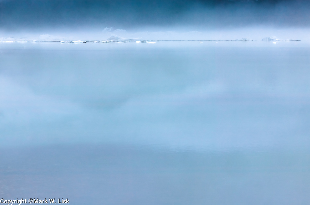 Fog rises from ice bergs on Alsek Lake giving an eerie feel to a summer day in Glacier Bay National Park, Alaska.