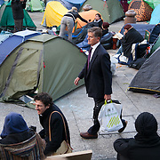A manin a pin-striped suit making his way through the camp. Day three of the occupation - and the first Monday.  The Occupy London Stock Exchange movement was formed in London in solidarity with the US based Occupy Wall Street. The movements are a respons and in anger to what is seen by many as corporate greed and a failed banking system being bailed out by the public, - which in return are suffering austerity measures to make up for the billions of lost money. The movement occupied the St Paul's Square in the City of London Sat Oct 15 after it failed to secure and occupy Pator Noster Square and the Stock Exchnage itself.