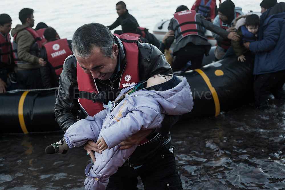 A migrant man carries aways a baby as refugees from Afghanistan and Syria frantically disembark from a rubber boat on the shores of Lesbos near Skala Sikaminias, Greece on 03 November, 2015. Lesbos, the Greek vacation island in the Aegean Sea between Turkey and Greece, faces massive refugee flows from the Middle East countries.