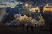CALAIS, FRANCE - OCT 22: Smoke rises after French police fire tear gas into the 'jungle' camp in response to refugees and migrants throwing stones towards police vans in Calais, France on October 22, 2016.