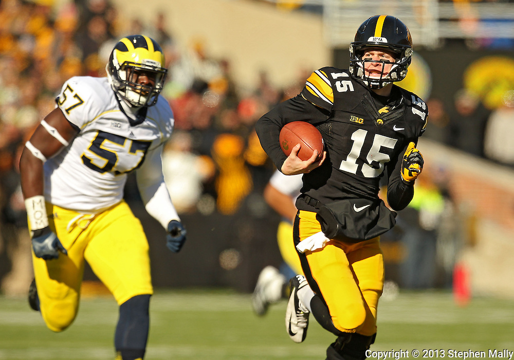 November 23 2013: Iowa Hawkeyes quarterback Jake Rudock (15) scrambles with the ball as Michigan Wolverines defensive end Frank Clark (57) gives chase during the first quarter of the NCAA football game between the Michigan Wolverines and the Iowa Hawkeyes at Kinnick Stadium in Iowa City, Iowa on November 23, 2013. Iowa defeated Michigan 24-21.