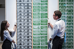 "© Licensed to London News Pictures. 08/06/2015. London, UK. Sotheby's technicians show ""One Dollar Bills"" by Andy Warhol (est. £12m - £18m), at the preview of ""To the Bearer on Demand"", a private collection of 21 works inspired by the US dollar, including Andy Warhol masterpieces, which will be auctioned on 1 and 2 July.  The collection is estimated to realise £50 million. Photo credit : Stephen Chung/LNP"