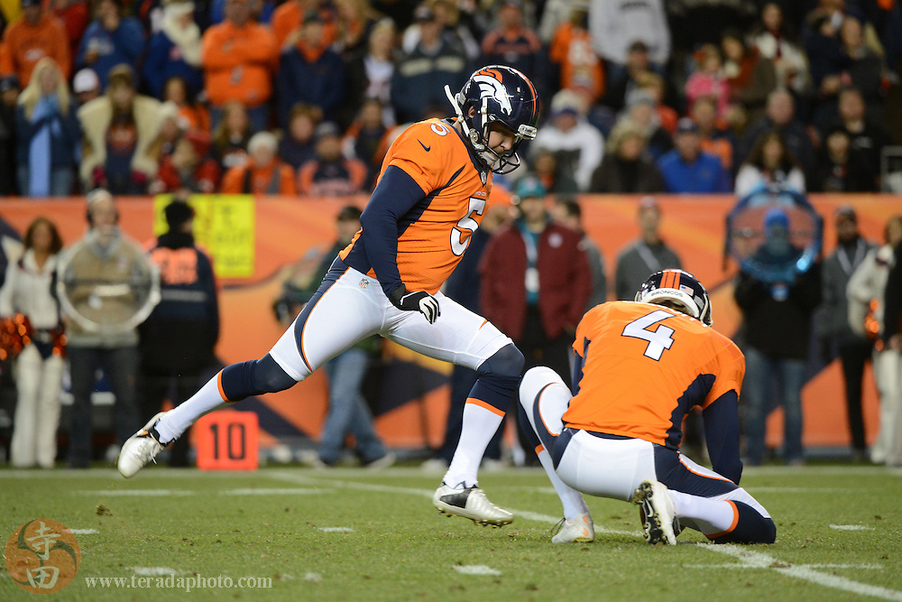 November 17, 2013; Denver, CO, USA; Denver Broncos kicker Matt Prater (5) kicks out of the hold by punter Britton Colquitt (4) during the first quarter against the Kansas City Chiefs at Sports Authority Field at Mile High. The Broncos defeated the Chiefs 27-17.