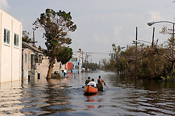 05 Sept  2005. New Orleans, Louisiana. Post hurricane Katrina.<br /> he Smith family paddle through the murky water in Uptown New Orleans as the family attempt to rescue their business.<br /> Photo; ©Charlie Varley/varleypix.com
