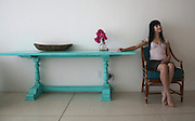 Woman smiling and sitting next to turquoise table with bugambilia flowers.<br />