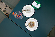 coffee cups and a glass on a table at an outdoors tourist destination