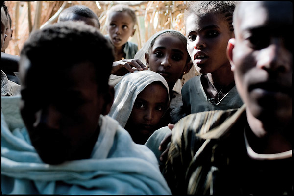 """Two child brides (in the middle), Jerusalem (above) 8 years old, and Ishalem,  age of 6, look at the people dancing at their marriage's celebration. In Ethiopia survives the practice of forced child marriage, even though the legal age to get married is 18. North West of Ethiopia, on friday, Febrary 13 2009.....In a tangled mingling of tradition and culture, in the normal place of living, in a laid-back attitude. The background of Ethiopia's """"child brides"""", a country which has the distinction of having highest percentage in the practice of early marriages despite having a law that establishes 18 years as minimum age to get married. Celebrations that last days, their minds clouded by girls cups of tella and the unknown for the future. White bridal veil frame their faces expressive of small defenseless creatures, who at the age ranging from three to twelve years shall be given to young brides men adults already...To protect the identities of the recorded subjects names and specific places are fictional."""