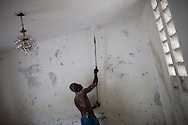 A man paints the inside of a house that was repaired after sustaining earthquake damage on July 5, 2010 in Port-au-Prince, Haiti.