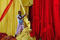 Inde, Rajasthan, Usine de Sari, Mango Singh, 60 ans. Les tissus sechent en plein air. Ramassage des tissus secs par des femmes et des enfants avant le repassage. Les tissus pendent sur des barres de bambou. Les rouleaux de tissus mesurent environ 800 m de long. <br />  // India, Rajasthan, Sari Factory, Mango Singh, 60 old. Textile are dried in the open air. Collecting of dry textile  are folded by women and children. The textiles are hung to dry on bamboo rods. The long bands of textiles are about 800 metre in length.