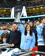 A Manchester City fan with a cut out of the League Cup at full time during the celebrations after City won the penalty shoot out after the match finished 0-0 during the Carabao Cup Final match between Chelsea and Manchester City at Wembley Stadium, London, England on 24 February 2019.