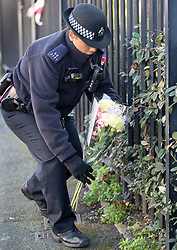 © Licensed to London News Pictures. 07/03/2019. London, UK. A police officer places a floral tribute, brought by a member of the public, next to the crime scene in North Birkbeck Road in Leyton in east London where a murder investigation has been launched after a man in his twenties was stabbed on Wednesday. Photo credit: Peter Macdiarmid/LNP