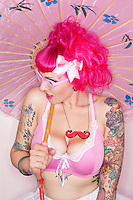 Side view of tattooed woman holding parasol