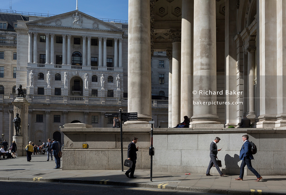 Londoners walk beneath the classical architecture of Royal Exchange (R) and the Bank of England (L), at Bank Triangle, on 10th May 2017, in the City of London, England.
