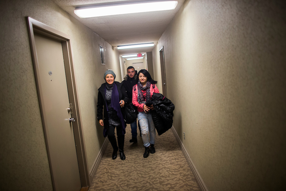 Syrian refugees Fusie Batal Al Hasan (right), her brother Ali Batal Al Hasan (centre), and their translator Mariela Barazi (left) walk down the hallway of their apartment building in Mississauga, Ontario, Canada, Thursday January 21, 2016.   (Mark Blinch for the BBC)