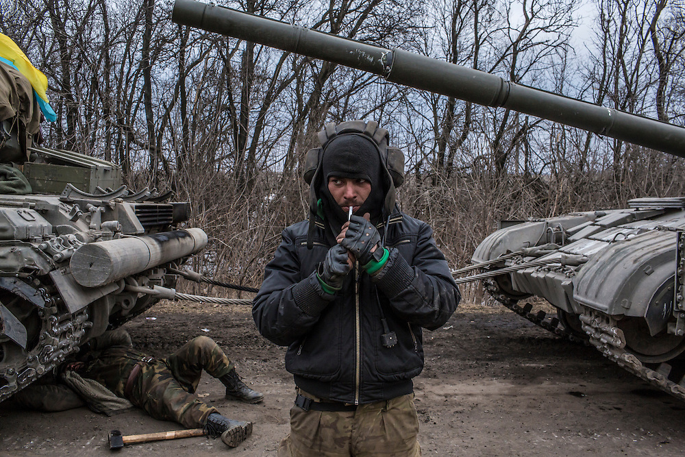 A Ukrainian soldier lights a cigarette while his unit's tank is repaired on a roadside leading out of Debaltseve on February 19, 2015 in Artemivsk, Ukraine. Ukrainian forces have begun withdrawing from the strategic and hard-fought town of Debaltseve after being effectively surrounded by pro-Russian rebels.