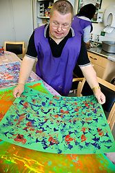 Day Service user with learning disability with her finished painting looked on by Day Service Officer,