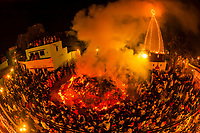 A crowd of 20,000 spectators surround a massive Holika bonfire at 4 AM just after a holy man has run through it on Purnima (the full moon) the night before Holi (the festival of colors) in the remote village of Falen, Uttar Pradesh, India.