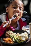 11月25日, 民众享用节日大餐。当天,在美国洛杉矶感恩节前夕,慈善社团为数千贫民区(Skid Row)居民和无家可归者提供免费节日大餐。(新华社发 赵汉荣摄)<br /> A girl takes her Thanksgiving meal Wednesday November 25, 2015, in Los Angeles. Thousands of Skid Row residents and homeless people from downtown and beyond were served Thanksgiving dinners during the Los Angeles Mission's annual holiday feast.  (Xinhua/Zhao Hanrong)(Photo by Ringo Chiu/PHOTOFORMULA.com)<br /> <br /> Usage Notes: This content is intended for editorial use only. For other uses, additional clearances may be required.