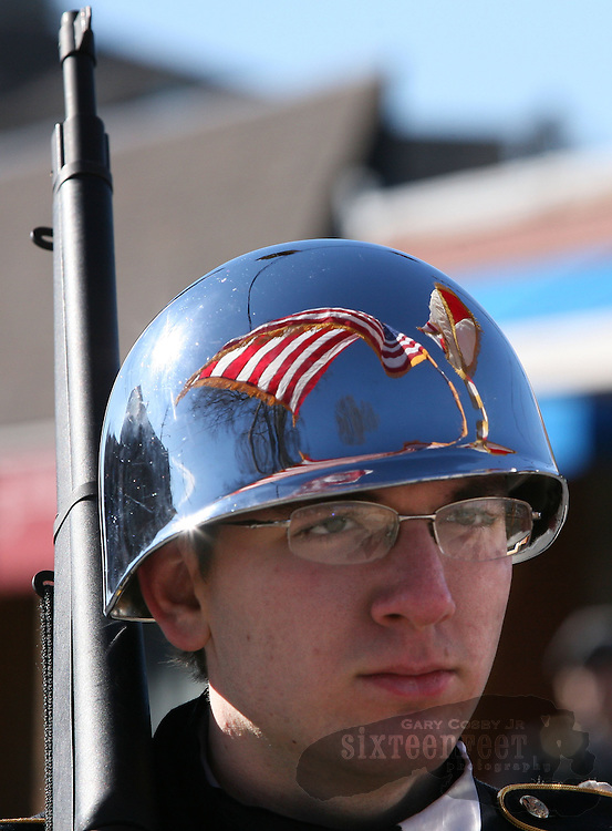 Gary Cosby Jr./Decatur Daily   Marchers parade around the town square in Athens Saturday in honor of Martin Luther King Jr.  The state and national flags reflect in the helmet of a member of the Athens High School JROTC honor guard as they lead the parade.