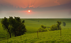 The morning sun dramatically rises on the prairie along the Flint Hills National Scenic Byway (Kansas State Highway 177) in the Kansas Flint Hills in Chase County, near the Tallgrass Prairie National Preserve. Less than four percent of the original 140 million acres of tallgrass prairie remains in North America. Most of the remaining tallgrass prairie is in the Flint Hills in Kansas.