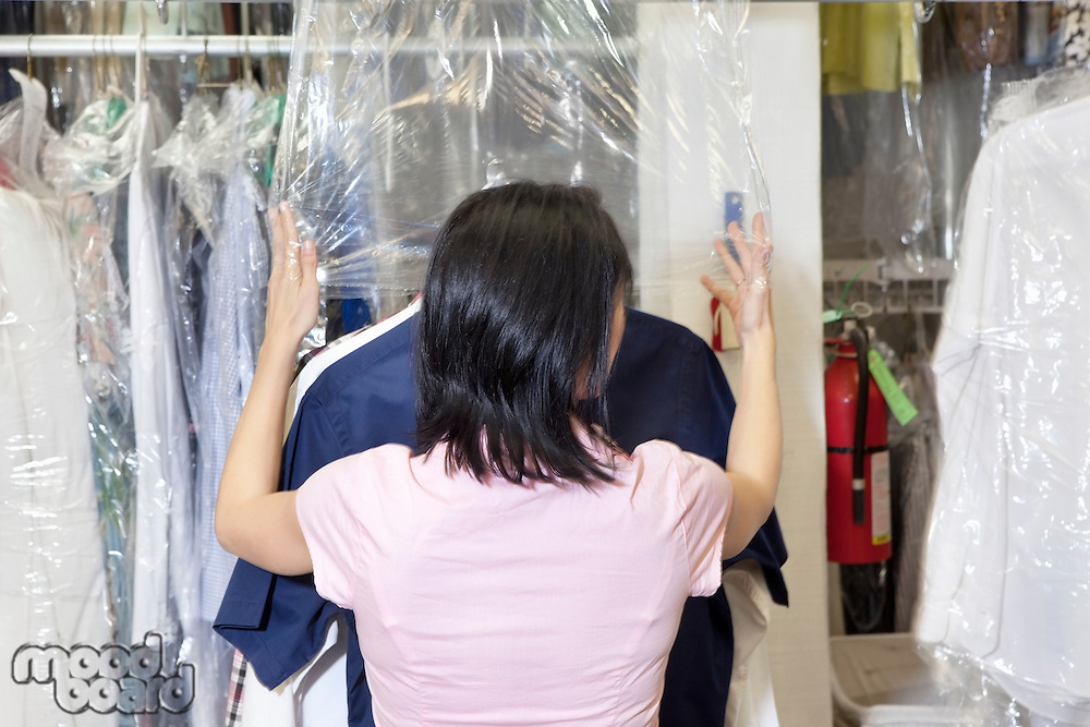 Back view of a mid adult employee putting plastic on dry cleaned clothes