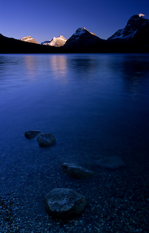 A few stones remain on the surface on the shore of Bow Lake, in Banff National Park, Alberta, as the sun is setting and lights up two distant mountains