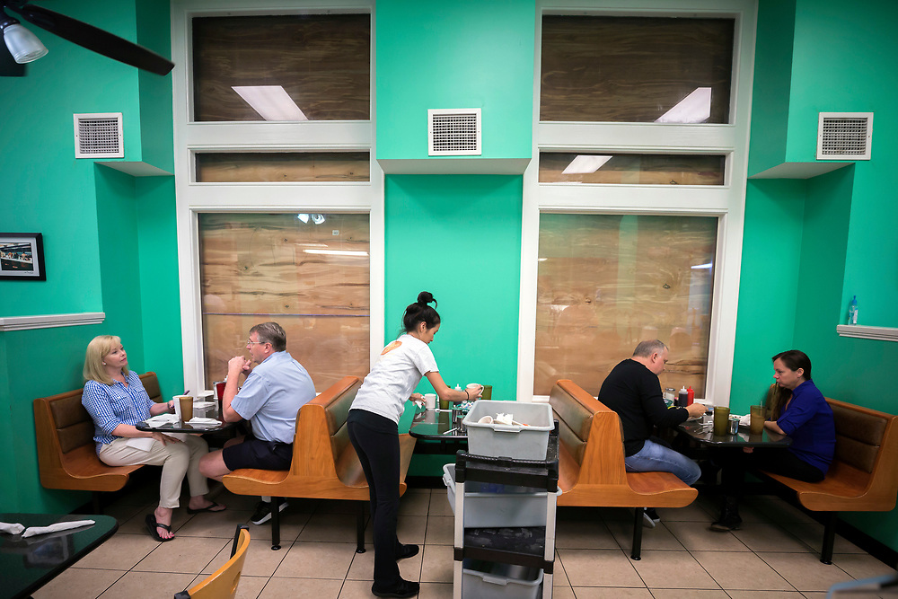 Henry's Restaurant manager Nhi Brayman, center, cleans a table while customers eat breakfast behind boarded up windows,, Sunday, Sept., 10, 2017 in downtown Savannah, Ga. Hurricane Irma is expected effect parts of Georgia as early as Sunday night. (AP Photo/Stephen B. Morton)