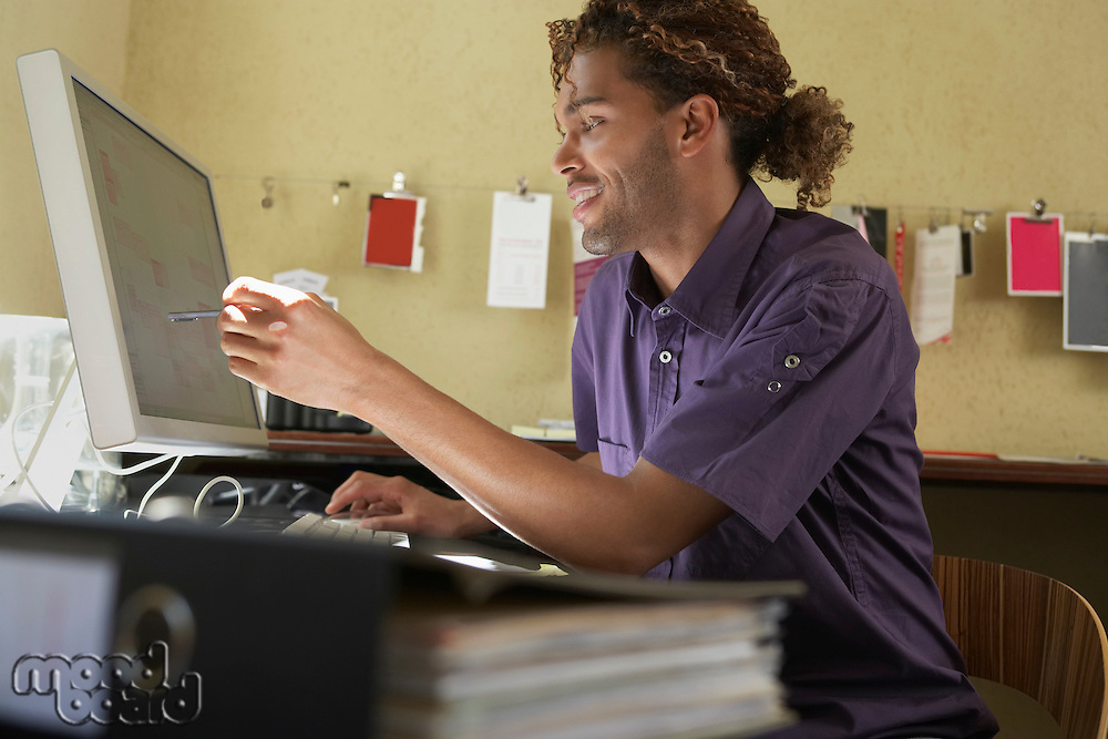 Young man pointing at computer screen in office